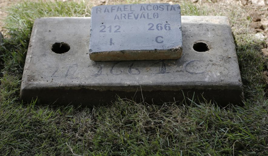 The tomb of Navy Captain Rafael Acosta lies at the East cemetery in Caracas, Venezuela, Wednesday July 10, 2019. Acosta, a Venezuelan navy captain who died of suspected torture while in government custody, was buried by authorities against the family's wishes to perform a private ceremony, an attorney and relatives said. (AP Photo/Leonardo Fernandez)
