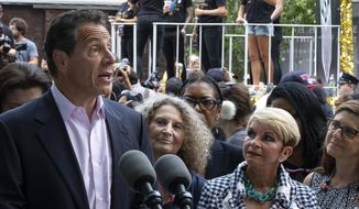 With members of the U.S. women's soccer team in the background before the start of a ticker tape parade in their honor, Gov. Andrew Cuomo speaks before signing a bill into law Wednesday, July 10, 2019, in New York. The bill will expand a law banning gender pay discrimination to make it illegal for employers to pay workers differently based on their age, race, religion or other characteristics, and making it easier for workers to prove pay discrimination in court. (AP Photo/Craig Ruttle)