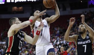 Washington Wizards' Justin Robinson shoots around Atlanta Hawks' Matt Mooney, left, and Amine Noua during the first half of an NBA summer league basketball game Thursday, July 11, 2019, in Las Vegas. (AP Photo/John Locher)