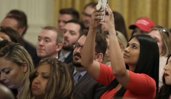 """An invited guest takes a photo as President Donald Trump speaks during the """"Presidential Social Media Summit"""" in the East Room of the White House, Thursday, July 11, 2019, in Washington. (AP Photo/Evan Vucci)"""