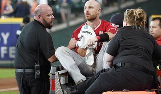 Los Angeles Angels' Jonathan Lucroy, center, is carted off the field after colliding with Houston Astros' Jake Marisnick at home plate during the eighth inning of a baseball game Sunday, July 7, 2019, in Houston. (AP Photo/David J. Phillip)