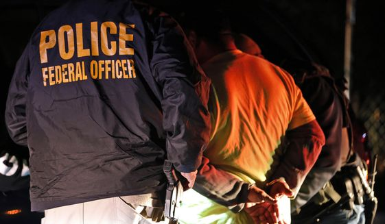 In this Oct. 22, 2018, file photo, U.S. Immigration and Customs Enforcement agents detain a person during a raid in Richmond, Va. Early in the morning of August 13, 2019, an unknown shooter took aim and shattered windows for a federal office building in San Antonio, Texas, that houses a field office for the agency. No injuries resulted from the incident and authorities are searching for the shooter. (AP Photo/Steve Helber, File) **FILE**
