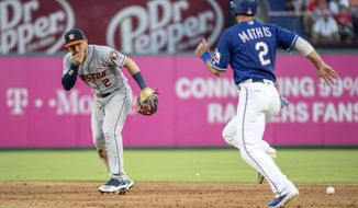 Houston Astros shortstop Alex Bregman (2) reacts after being hit in the face by a ground ball by Texas Rangers' Shin-Soo Choo as Jeff Mathis (2) runs towards second during the third inning of a baseball game Thursday, July 11, 2019, in Arlington, Texas. Bregman left the game because of the injury. (AP Photo/Jeffrey McWhorter)
