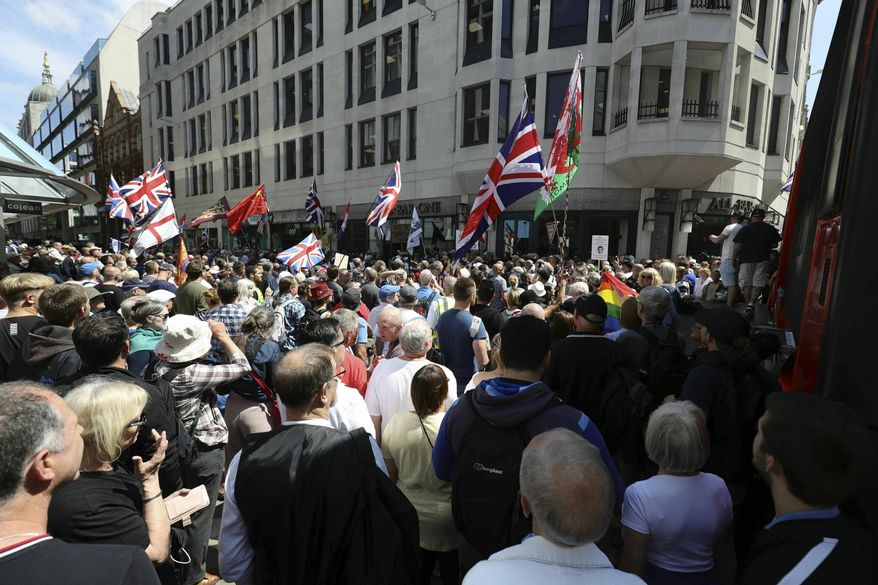 Tommy Robinson supporters stand outside the Old Bailey courthouse in London, Thursday, July 11, 2019. A British judge has sentenced far-right activist Stephen Yaxley-Lennon to a total of nine months in prison for contempt of court. Yaxley-Lennon, who uses the pseudonym Tommy Robinson, was arrested and jailed last year for potentially prejudicing a trial after the Facebook broadcast outside a trial of men accused of sexually abusing teenage girls. (Aaron Chown/PA via AP)
