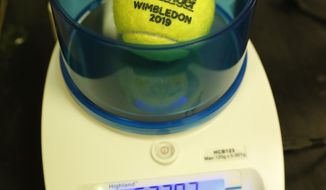 In this photo taken Friday June, 28, 2019, a Wimbledon 2019 tennis ball is weighed at the International Tennis Federation (ITF) lab in Roehampton, near Wimbledon south west London. Based for about 20 years in a three-room area on what used to be a pair of squash courts in Roehampton, the ITF tech lab is filled with more than $1 million worth of machines that help make sure rules are followed and parameters are met. (AP Photo/Alastair Grant)