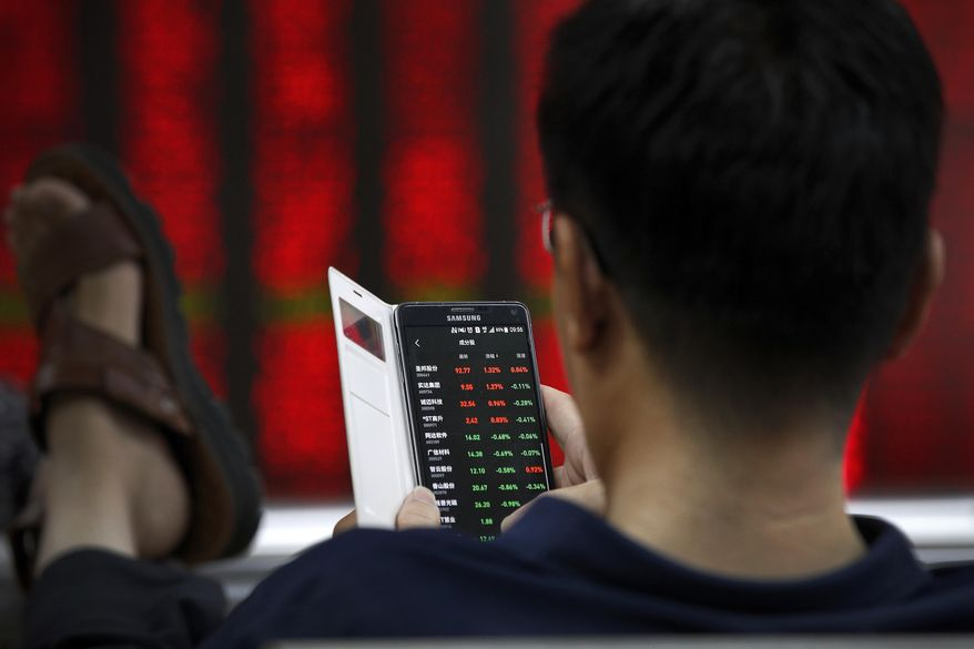A man checks stock prices through his smartphone at a brokerage house in Beijing, Thursday, July 11, 2019. Shares rose Thursday in Asia, tracking gains on Wall Street after Federal Reserve Chairman Jerome Powell suggested the U.S. central bank is ready to cut interest rates for the first time in a decade. (AP Photo/Andy Wong)