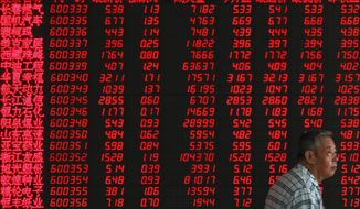An investor walks by an electronic board displaying stock prices at a brokerage house in Beijing, Thursday, July 11, 2019. Shares rose Thursday in Asia, tracking gains on Wall Street after Federal Reserve Chairman Jerome Powell suggested the U.S. central bank is ready to cut interest rates for the first time in a decade. (AP Photo/Andy Wong)