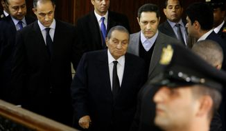 FILE - In this Dec. 26, 2018 file photo, former Egyptian President Hosni Mubarak, center, arrives with his sons Alaa, left, and Gamal, right, to testify, in a courtroom at the National Police Academy in the Egyptian capital, Cairo. Egypt has arrested the administrator of a Facebook page that supports former President Hosni Mubarak, who was forced from power by a pro-democracy uprising in 2011. Prosecutors on Thursday, July 11, 2019, charged Karim Hussein with spreading false news and undermining national interests after a series of posts that implied Mubarak did more to help the poor than the current government. (AP Photo/Ahmed Abdel Fattah, File)