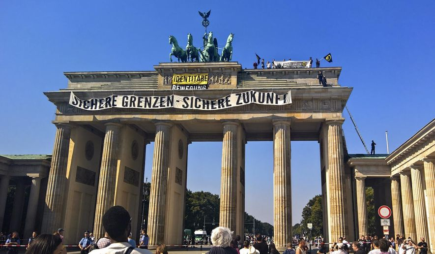 FILE - In this Aug. 27, 2016 file photo, activists of the Identitarian Movement protest on the Brandenburg Gate in Berlin, Germany, with a banner reading 'secure borders - secure future'. The German domestic intelligence agency says it is stepping up observation of the far-right Identitarian Movement in Germany that campaigns against immigrants and Islam. (AP Photo/Frank Jordans)