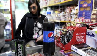 An Iranian Customer buys a Pepsi in a grocery store in downtown Tehran, Iran, Wednesday, July 10, 2019. Whether at upscale restaurants or corner stores, American brands like Coca-Cola and Pepsi can be seen throughout Iran despite the heightened tensions between the two countries. U.S. sanctions have taken a heavy toll, but Western food, movies, music and clothing are still widely available. (AP Photo/Ebrahim Noroozi)