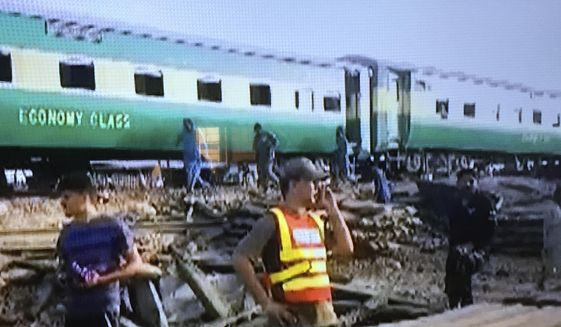 In this image made from video from Geo Tv, shows volunteers working at a train crash site in Rahim Yar Khan, Pakistan, Thursday, July 11, 2019. A passenger train rammed into a freight train in southern Pakistan on Thursday, killing at least many people and injuring others, an official said. (Geo Tv via AP)