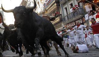 Revellers run next to fighting bulls during the running of the bulls at the San Fermin Festival, in Pamplona, northern Spain, Thursday, July, 11, 2019. Revellers from around the world flock to Pamplona every year to take part in the eight days of the running of the bulls. (AP Photo/Alvaro Barrientos)