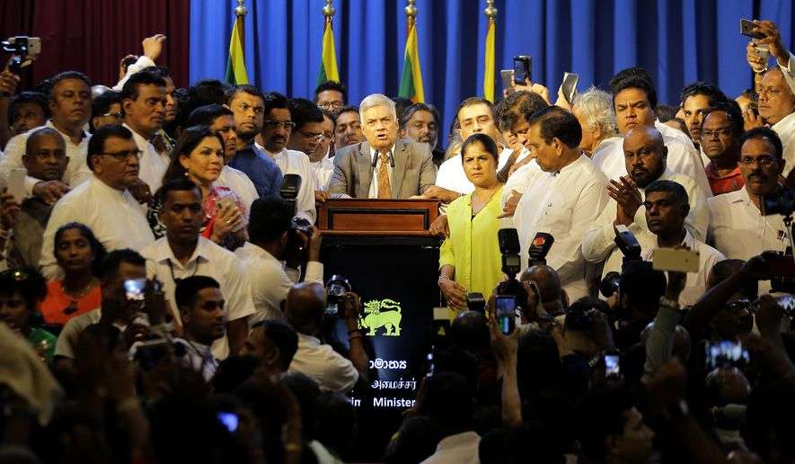 In this Sunday, Dec. 16, 2018, file photo, Sri Lanka's reinstated Prime Minister Ranil Wickremesinghe, center, surrounded by his loyal lawmakers and supporters speaks after assuming duties in Colombo, Sri Lanka. Sri Lanka's government has defeated a no-confidence motion in Parliament on Thursday, July 11, that accused it of failing to prevent Easter Sunday bomb attacks that killed more than 250 people. The motion against Wickremesinghe's government was defeated by a vote of 119 lawmakers against the measure to 92 in favor. (AP Photo/Eranga Jayawardena, File)