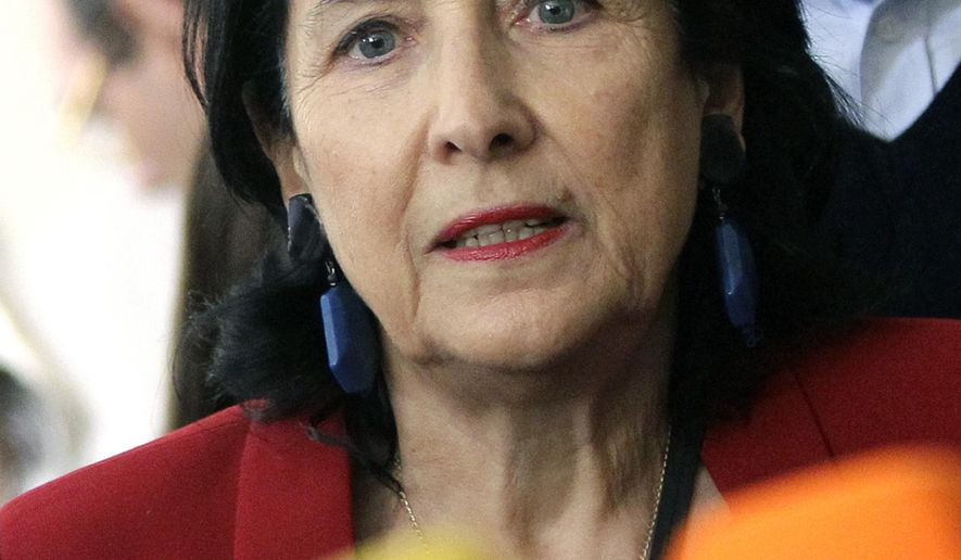 In this photo taken on Sunday, Oct. 28, 2018, Salome Zurabishvili speaks to the media at a polling station during the presidential election in Tbilisi, Georgia. During an interview Thursday July 11, 2019, Zurabishvili said she'll wait and see how possible new sanctions against her country will pan out, as she cautiously welcomed conciliatory comments from President Vladimir Putin. (AP Photo/Shakh Aivazov, File)