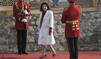 "FILE In this file photo taken on Sunday, Dec. 16, 2018, Georgian President Salome Zurabishvili arrives to attend her inauguration in Telavi, Georgia. Georgia's president says she'll ""wait and see"" how a debate in Russia about possible new sanctions against her country will shape out, cautiously welcoming conciliatory comments from President Vladimir Putin as preferable to ""threats."". (Irakli Gedenidze/Pool Photo via AP, File)"