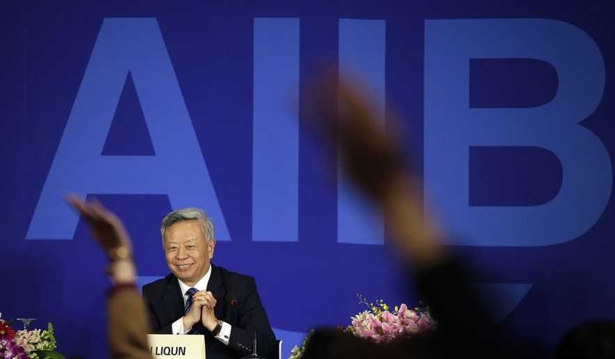 Jin Liqun, inaugural president of the Asian Infrastructure Investment Bank (AIIB), smiles as reporters raise their hands to ask for questions during a press conference at a hotel in Beijing on Jan. 17, 2016. (Associated Press) **FILE**