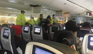 """In this photo provided by Hurricane Fall, responders treat a passenger on an Air Canada flight to Australia that was diverted and landed at Daniel K. Inouye International Airport in Honolulu on Thursday, July 11, 2019. The flight from Vancouver to Sydney encountered """"un-forecasted and sudden turbulence,"""" about two hours past Hawaii when the plane diverted to Honolulu, Air Canada spokeswoman Angela Mah said in a statement. (Tim Tricky/Hurricane Fall via AP)"""