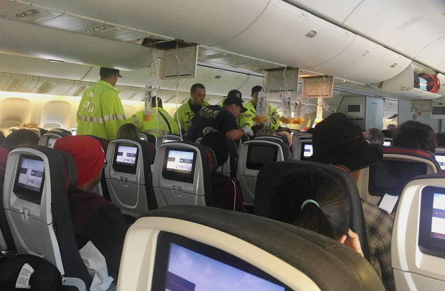 "In this photo provided by Hurricane Fall, responders treat a passenger on an Air Canada flight to Australia that was diverted and landed at Daniel K. Inouye International Airport in Honolulu on Thursday, July 11, 2019. The flight from Vancouver to Sydney encountered ""un-forecasted and sudden turbulence,"" about two hours past Hawaii when the plane diverted to Honolulu, Air Canada spokeswoman Angela Mah said in a statement. (Tim Tricky/Hurricane Fall via AP)"