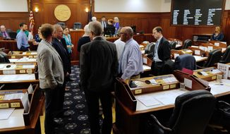 Lawmakers talk among themselves during a break of a joint session of the Alaska Legislature Thursday, July 11, 2019, in Juneau, Alaska. Lawmakers are meeting for a second day to consider overriding Gov. Mike Dunleavy's budget vetoes, but still don't have the needed 45 votes as about a third of lawmakers continue to meet in Wasilla instead of Juneau. (Michael Penn/The Juneau Empire via AP)