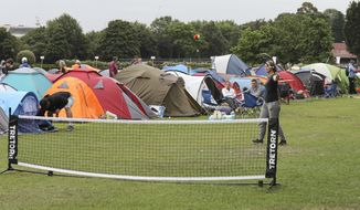 "In this Tuesday, July 9, 2019, some tennis fans play a game as they wait in line for tickets to enter the Wimbledon Tennis Championships in London. For many the Wimbledon experience starts in a tent as they gather in a small park across from the tournament grounds to camp out, some for days, in the hope of getting a ticket to Centre Court as they are released each day. ""The Queue"" is a decades-old tradition that has grown to become its own phenomenon.(AP Photo/Natasha Livingstone)"