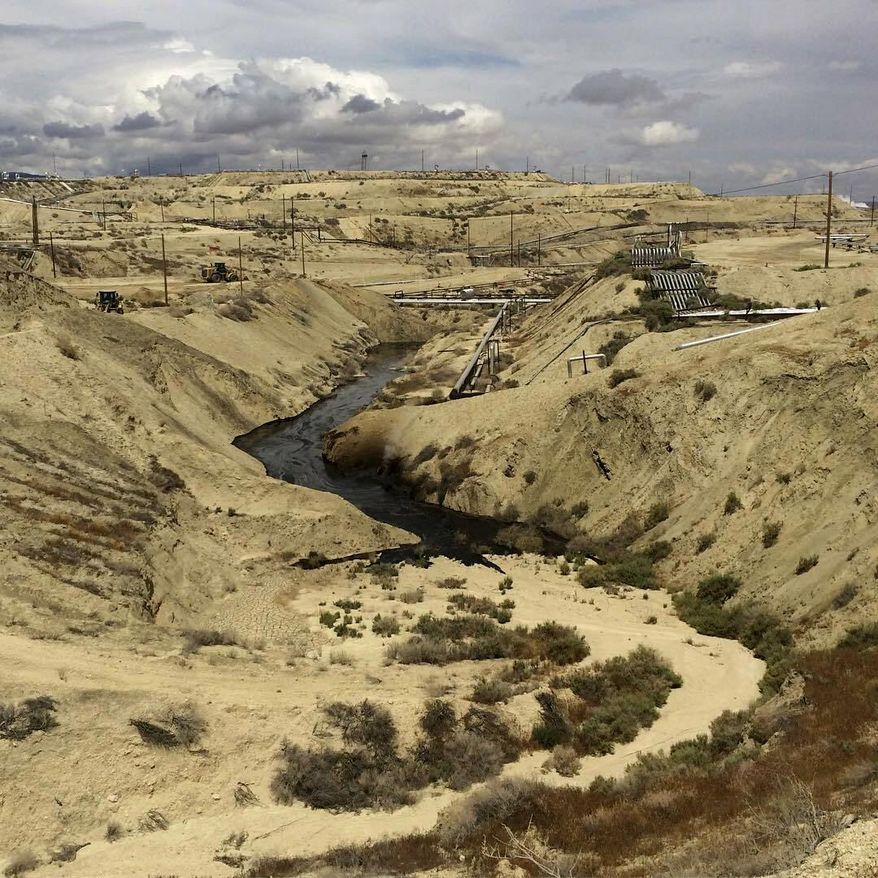 In this May 10, 2019, file photo provided by the California Department of Fish and Wildlife's Office of Spill Prevention and Response, oil flows at a Chevron oil field in Kern County, Calif. Nearly 800,000 gallons of oil and water has seeped from the ground since May. Chevron and California officials say the spill is not near any waterway and has not significantly affected wildlife. (California Department of Fish and Wildlife's Office of Spill Prevention and Response via AP)