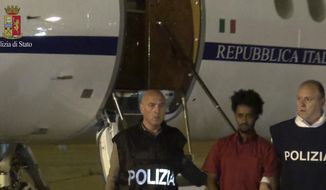 FILE - This June 7, 2016 file photo taken from a video and released by the Italian Police shows a man identified by prosecutors as Medhane Yehdego Mered, center, a 35-year-old Eritrean, arrested two weeks earlier in Sudan, upon his arrival at Ciampino's airport, on the outskirts of Rome. On Friday, July 12, 2019, a court in Sicily will deliberate the fate of alleged migrants smugglers, including an Eritrean who claims his is a case of mistaken ID. The defendant's lawyer, Michele Calantropo contends the defendant's identity is Medhanie Tesfamariam Behre and that he's innocent, prosecutors insist his client is Medhane Yehdego Mered, an alleged human trafficking kingpin. ( Italian Police via AP/files)