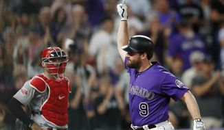 Colorado Rockies' Daniel Murphy gestures as he crosses home plate after hitting a solo home run, next to Cincinnati Reds catcher Curt Casali during the eighth inning of a baseball game Friday, July 12, 2019, in Denver. The Rockies won 3-2. (AP Photo/David Zalubowski)