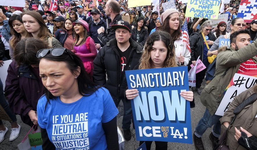 "In this Feb. 18, 2017, file photo, thousands of people take part in the ""Free the People Immigration March,"" to protest actions taken by President Donald Trump and his administration, in Los Angeles. A federal appeals court has given the Trump administration a rare legal win in its efforts to crack down on sanctuary cities. In a 2-1 decision Friday, July 12, 2019, the 9th U.S. Circuit Court of Appeals said the Justice Department was within its rights to give priority status for multimillion-dollar community policing grants to departments that agree to cooperate with immigration officials.  (AP Photo/Ringo H.W. Chiu, File)"