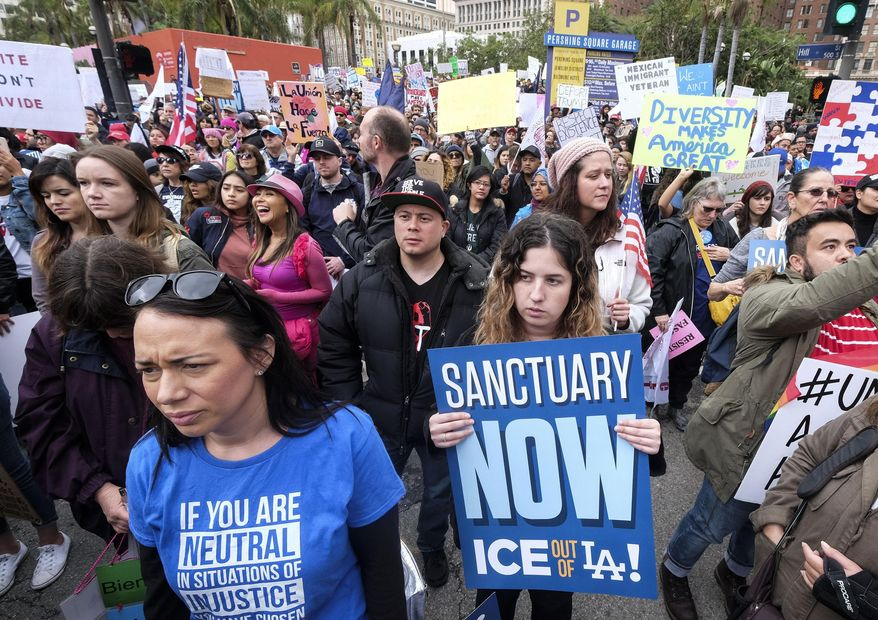"""In this Feb. 18, 2017, file photo, thousands of people take part in the """"Free the People Immigration March,"""" to protest actions taken by President Donald Trump and his administration, in Los Angeles. A federal appeals court has given the Trump administration a rare legal win in its efforts to crack down on sanctuary cities. In a 2-1 decision Friday, July 12, 2019, the 9th U.S. Circuit Court of Appeals said the Justice Department was within its rights to give priority status for multimillion-dollar community policing grants to departments that agree to cooperate with immigration officials.  (AP Photo/Ringo H.W. Chiu, File)"""