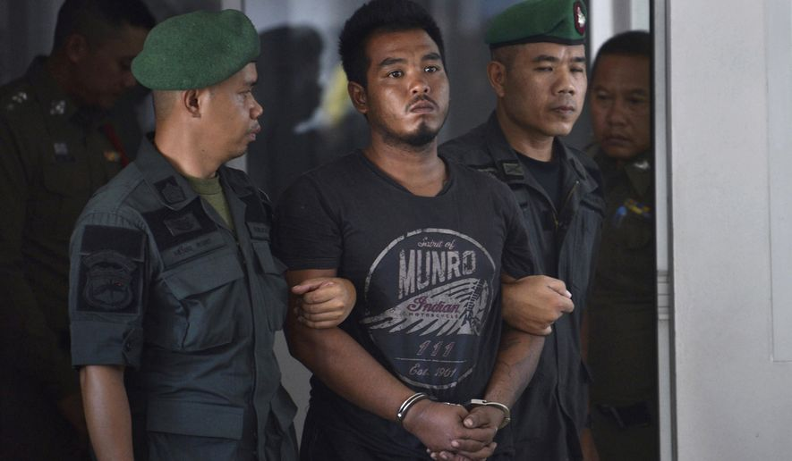 FILE - in this April 9, 2019, file photo, Thai suspect Ronnakorn Romruen, center, is escorted by police as he arrives at the Koh Sichang police station in Chonburi province, Thailand. Ronnakorn was sentenced to death Wednesday, July 10, 2019 by the Chonburi provincial court for raping and murdering a German tourist on the popular resort island after he confessed to carrying out the ordeal. (AP Photo, File)