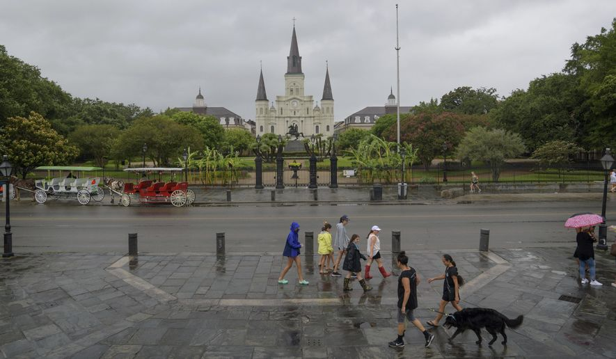 In this file photo from July 12, 2019, people walk past Jackson Square and St. Louis Cathedral in the French Quarter in New Orleans, La. (AP Photo/Matthew Hinton) **FILE**