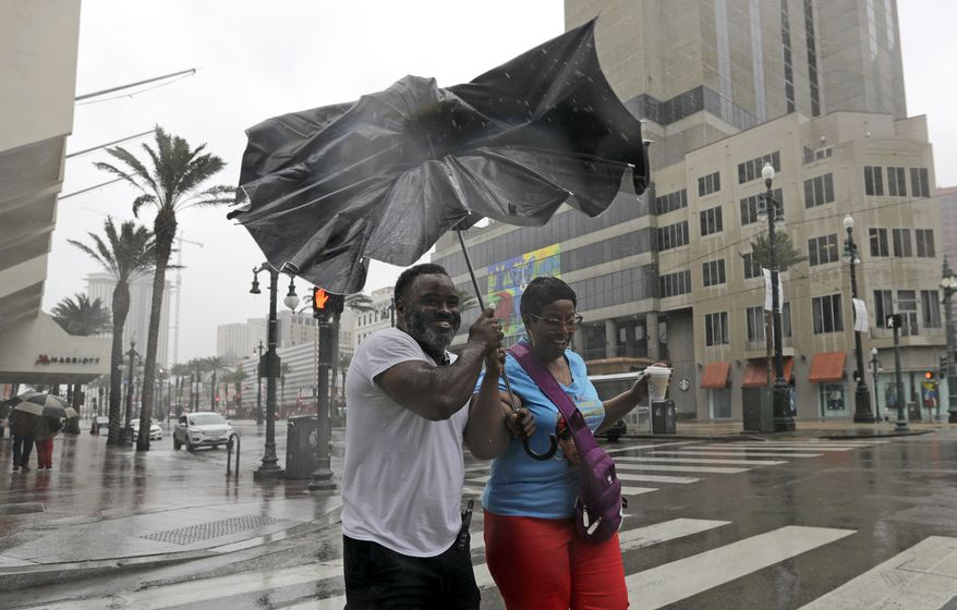Karon Hill, left, and Celeste Cruz battle the wind and rain from Hurricane Barry as it nears landfall Saturday, July 13, 2019, in New Orleans. (AP Photo/David J. Phillip)