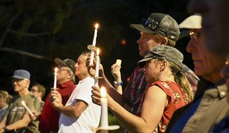 """People gather at Sayre Park in Glenwood Springs, Colo., for the """"Lights for Liberty"""" rally and candlelight vigil Friday, July 12, 2019, as part of a national campaign to call attention to migrant detention centers.  (Chelsea Self/Glenwood Springs Post Independent via AP)"""