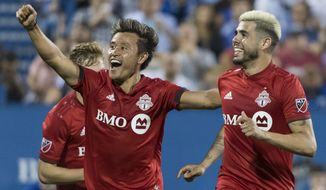 Toronto FC's Alejandro Pozuelo, right, celebrates with teammate Tsubasa Endoh after scoring during second-half MLS soccer match action against the Montreal Impact in Montreal, Saturday, July 13, 2019. (Graham Hughes/The Canadian Press via AP)