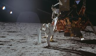 In this July 20, 1969 photo made available by NASA, Apollo 11 astronaut Buzz Aldrin works on a solar wind experiment device on the surface of the moon. (Neil Armstrong/NASA via AP)