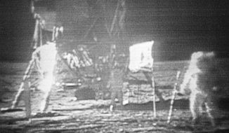 FILE - In this July 20, 1969 image made from television, Apollo 11 astronaut Neil Armstrong, right, trudges across the surface of the moon leaving behind footprints. The U.S. flag, planted on the surface by the astronauts, can be seen between Armstrong and the lunar module. Edwin E. Aldrin is seen closer to the craft. The men reported the surface of the moon was like soft sand and they left footprints several inches deep wherever they walked. (NASA via AP)
