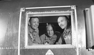 FILE - In this July 27, 1969 file photo, Apollo 11 crew members, from left, Neil Armstrong, Buzz Aldrin and Michael Collins sit inside a quarantine van in Houston. (AP Photo)