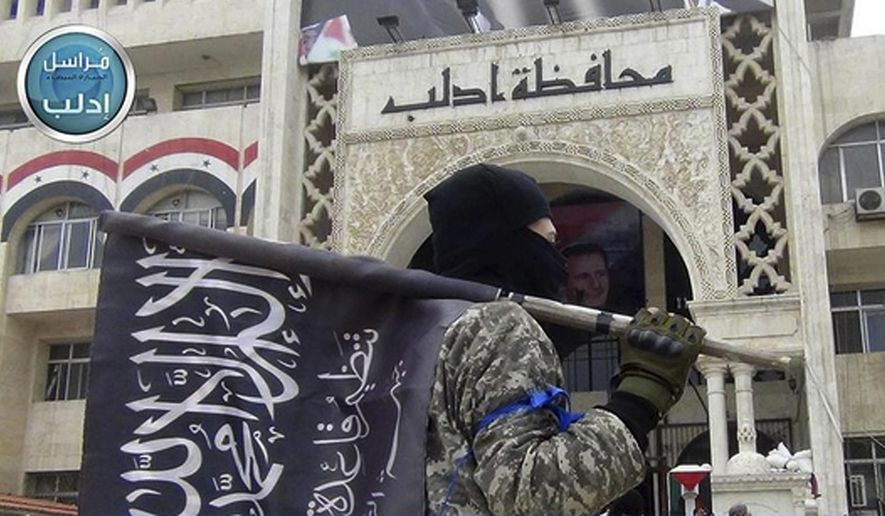 In this photo posted on the Twitter page of Syria's al Qaeda-linked Nusra Front on March 28, 2015, a fighter from Syria's al Qaeda-linked Nusra Front holds his group flag as he stands in front of the governor building in Idlib province, north Syria. (Al-Nusra Front Twitter page via AP) **FILE**