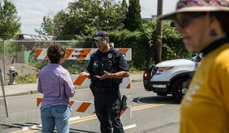 Police Officer Sam Lopez turns away would-be protesters in front of a road block near the Northwest Detention Center, Saturday July 13, 2019 in Tacoma, Wash. A man armed with a rifle threw incendiary devices at an immigration jail in Washington state early Saturday morning, then was found dead after four police officers arrived and opened fire, authorities said. (Rebekah Welch/The Seattle Times via AP)
