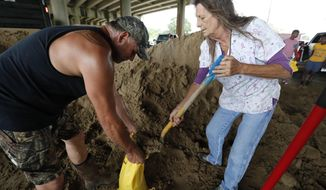"Judy Daigle, owner of ""The Chili House and More,"" right, helps Michael Fuselier fill a sandbag at one of several locations in Morgan City, La., Friday, July 12, 2019. Daigle's restaurant is across a parking lot from where the city provided sand for sandbagging. ""I just had to lend a hand to these folks,"" said Daigle. (AP Photo/Rogelio V. Solis)"