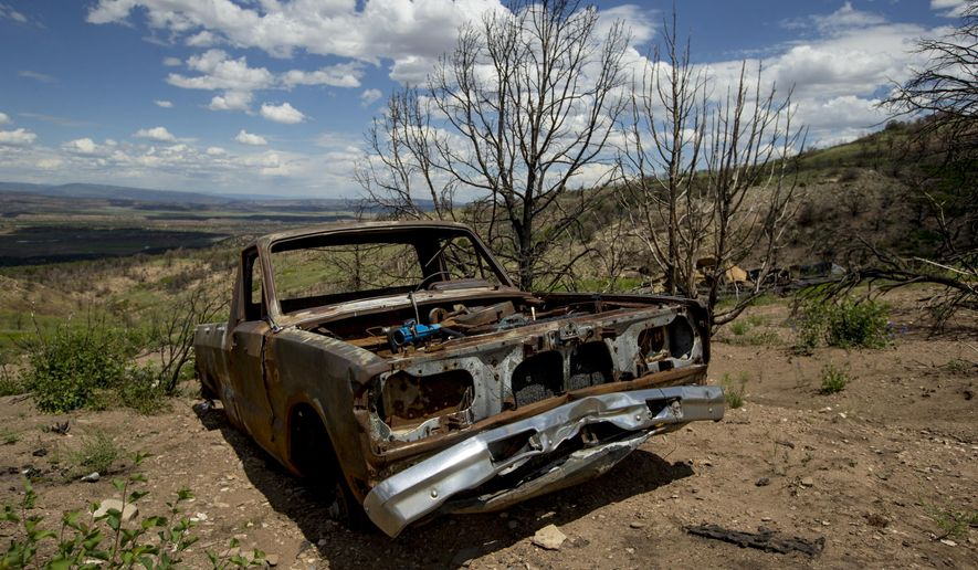 In this Monday, July 8, 2019 photo, a burned pickup truck remains beside where a mobile home once stood during a tour to examine conditions near the Wildcat Wildlife Management Area roughly a year after a wildfire in Duchesne County, Utah. The Daily Herald reports that grasses and flowers are returning to the area alongside charred trees. Other vegetation, like trees and sagebrush, are expected to take longer. (Isaac Hale/The Daily Herald via AP)