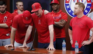 Los Angeles Angels' Mike Trout, left, embraces Andrew Heaney, center, who fights back tears as he answers questions about his late friend and teammate, Tyler Skaggs, after the Angels' baseball game against the Texas Rangers in Arlington, Texas, Tuesday, July 2, 2019.  (AP Photo/Tony Gutierrez)