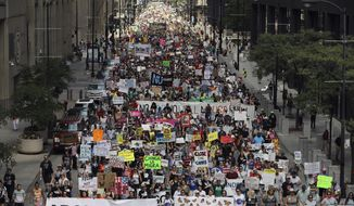 Thousands of people, including immigrants and their supporters, rally against President Trump's immigration policies as they march from Daley Plaza to the Chicago field office of Immigration and Customs Enforcement, Saturday, July 13, 2019, in Chicago. (Abel Uribe/Chicago Tribune via AP)