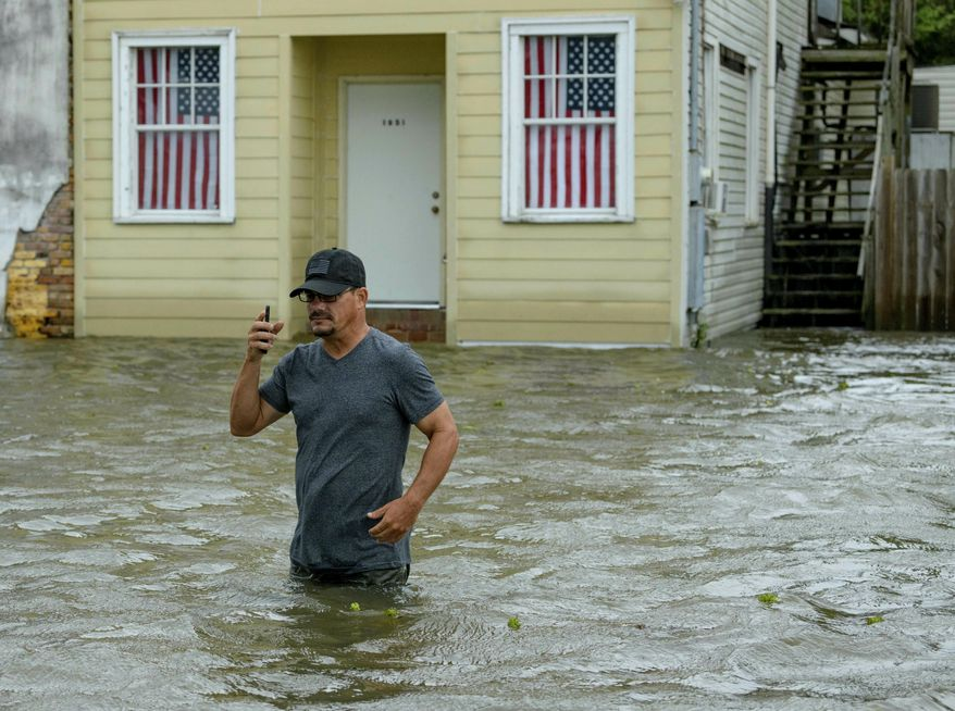 Barry Williams talks to a friend on his smartphone as he wades through storm surge from Lake Pontchartrain on Lakeshore Drive in Mandeville, La., as Hurricane Barry approaches Saturday, July 13, 2019.  After briefly becoming a Category 1 hurricane, the system quickly weakened to a tropical storm as it made landfall near Intracoastal City, Louisiana, about 160 miles (257km) west of New Orleans, with its winds falling to 70 mph (112km), the National Hurricane Center said.  (AP Photo/Matthew Hinton)