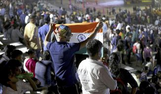 """An Indian spectator folds a flag as others leave after the Chandrayaan-2 mission was aborted at Sriharikota, in southern India, Monday, July 15, 2019. India has called off the launch of a moon mission to explore the lunar south pole. The Chandrayaan-2 mission was aborted less than an hour before takeoff on Monday. An Indian Space Research Organization spokesman says a """"technical snag"""" was observed in the 640-ton launch-vehicle system. (AP Photo/Manish Swarup)"""
