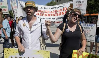 Thomas Muccioli and Allie Horton hold hands as they chant at the end of a march in opposition to the Trump administration's plans to continue with raids to catch immigrants in the country illegally, Sunday, July 14, 2019, in the Queens borough of New York. (AP Photo/Julius Constantine Motal)