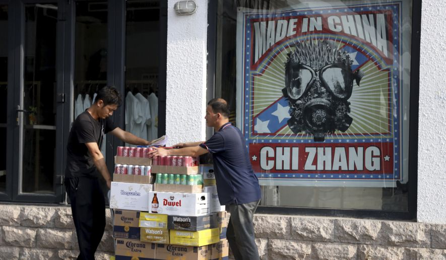 In this photo taken June 28, 2019, delivery men push cartons of beverage past a Chinese clothing store in Beijing. China's economic growth slowed to its lowest level in a decade in the quarter ending in June, adding to pressure on Chinese leaders as they fight a tariff war with Washington. (AP Photo/Ng Han Guan) ** FILE **