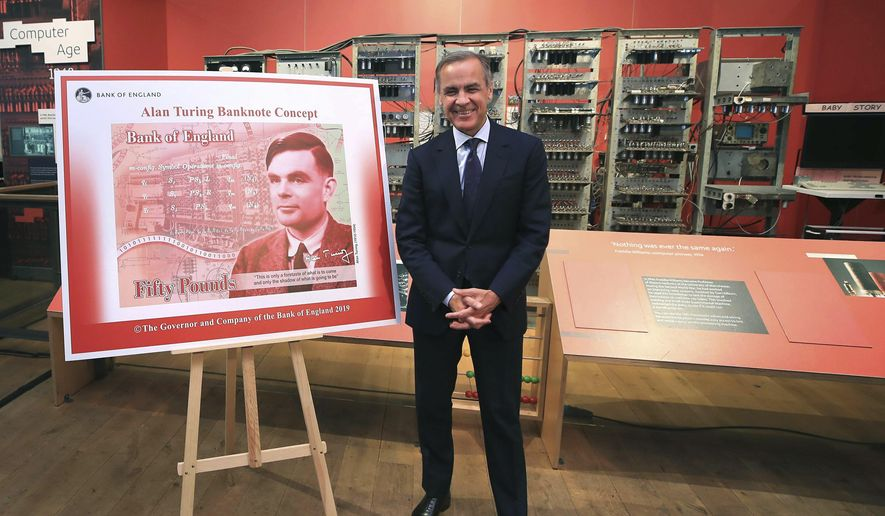 Governor of the Bank of England, Mark Carney, poses for a photo with the artwork for the concept of the new 50-pound notes, after announcing that Second World War code-breaker Alan Turing has been selected to feature on the new notes, at the Science and Industry Museum, in Manchester, England, Monday, July 15, 2019. (Peter Byrne/PA via AP)