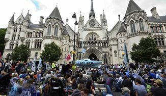 "Protesters from from the environmental pressure group Extinction Rebellion demonstrate outside the Royal Courts of Justice in London, Monday July 15, 2019.  Environmental campaigners are blocking some roads across the UK on Monday, as they protest against what they allege is ""inaction"" on climate change. (Kirsty O'Connor/PA via AP)"