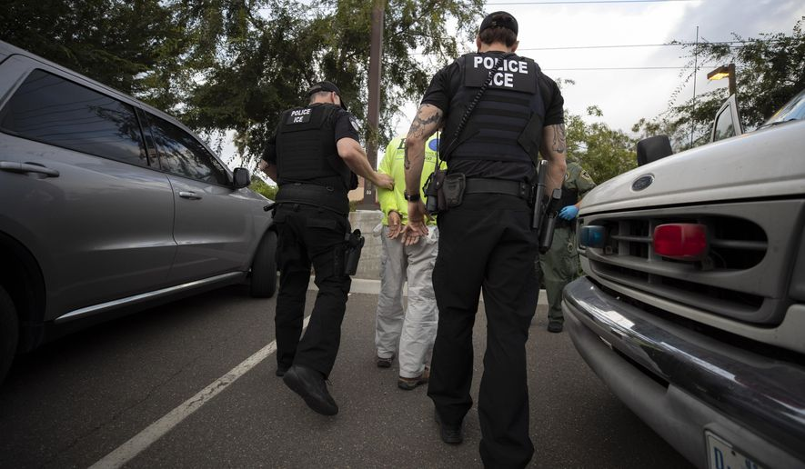 In this July 8, 2019, photo, a U.S. Immigration and Customs Enforcement (ICE) officers escort a man in handcuffs during an operation in Escondido, Calif. The carefully orchestrated arrest last week in this San Diego suburb illustrates how President Donald Trump's pledge to start deporting millions of people in the country illegally is virtually impossible with ICE's budget and its method of picking people up. (AP Photo/Gregory Bull) **FILE**